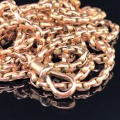 AN ANTIQUE 9ct GOLD CONTINUOUS GUARD MUFF CHAIN WITH DOG TOOTH CLASP, LENGTH 149cms, WEIGHT 28.8grms
