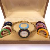 A GUCCI 1100-L GOLD PLATED LADIES BANGLE WATCH WITH TWELVE INTERCHANGEABLE BEZELS, COMPLETE WITH