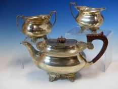 A HALLMARKED SILVER THREE PIECE TEA SET COMPRISING OF A TEAPOT, SUGAR AND CREAMER. DATED 1970