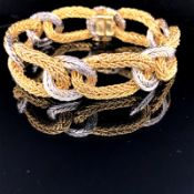 AN 18ct GOLD KUTCHINSKY BRACELET. COMPOSED OF A SERIES OF WHITE AND YELLOW GOLD OPEN TEXTURED