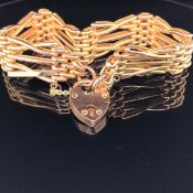 A 9ct GOLD THREE BAR TEXTURED GATE BRACELET COMPLETE WITH SAFETY CHAIN AND PADLOCK. WEIGHT 17.8grms.