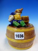 A 19th C. MAJOLICA TOBACCO BARREL, THE SLEEPING FIGURE OF A TOPER ON THE COVER WITH ONE ARM AROUND A