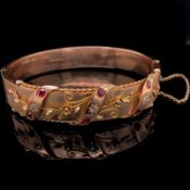 AN EDWARDIAN ANTIQUE 9ct OLD GOLD RUBY AND DIAMOND BANGLE, DATED 1910 FOR BIRMINGHAM. THE FRONT WITH