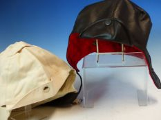 A BLACK LEATHER AND A WHITE CLOTH DRIVING HOOD, THE FORMER WITH QUILTED RED SILK LINING, THE