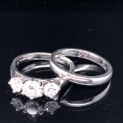 A PLATINUM AND DIAMOND THREE STONE DIAMOND RING SET WITH THREE GRADUATED BRILLIANT CUT DIAMONDS,