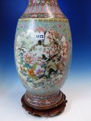 A CHINESE FAMILLE ROSE VASE WITH WOOD STAND, THE BALUSTER SHAPE PAINTED WITH RESERVES OF FLOWERS AND