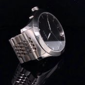 A GENTS GUCCI WATCH ON A STAINLESS STEEL BRACELET STRAP, WITH A BI-FOLDING CLASP. BLACK DIAL, DATE
