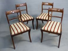 A SET OF FOUR REGENCY MAHOGANY DINING CHAIRS WITH ROPE RAIL BACK, DROP IN SEAT PADS ON SABRE
