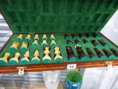 A TURNED WOOD CHESS SET IN FOLDING CHESS BOARD BOX.