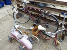 A GENTS BICYCLE, A SCOOTER, A VINTAGE TRICYCLE, A RIDE ON TOY SPORTS CAR, AND A FURTHER SCOOTER.