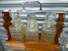 AN EDWARDIAN OAK AND SILVER PLATE MOUNTED THREE BOTTLE TANTALUS, BY ALEXANDER CLARK.