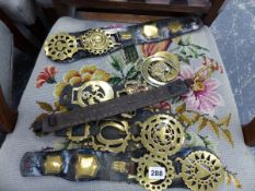 FOUR LEATHER MOUNTED DOUBLE HORSE BRASSES TWO LOOSE AND AND A LEATHER AND BRASS COLLAR.