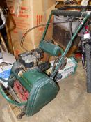 A PETROL PUSH MOWER WITH SCARIFIER CASSETTE ATTACHMENT.