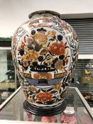 A LARGE ORIENTAL STYLE BALUSTER VASE IN IMARI PALETTE COLOURS WITH WOODEN BASE.