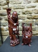 A CHINESE CARVED WOODEN FIGURE OF SHOULAO AS A LAMP, HE STANDS BY A CRANE OPENING A SCROLL. H 43cms.