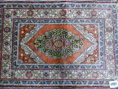 A PERSIAN SILK MAT, THE MEDALLION CENTRAL TO THE TERRACOTTA FIELD AND WHITE GROUND MAIN BORDER. 62 x