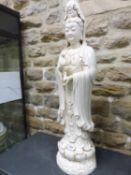 A BLANC DE CHINE FIGURE OF GUANYIN STANDING ON A DOUBLE LOTUS PLINTH, HER RIGHT HAND RAISED IN