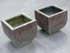 A PAIR OF COPPER PLANTERS, THE SQUARE RIMS ABOVE SIDES ROUNDING DOWN TO THE PIERCED FEET. W 35 x D