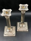 A PAIR OF HALLMARKED WEIGHTED SILVER CORINTHIAN COLUMN CANDLESTICKS ON SQUARE STEP BASES WITH