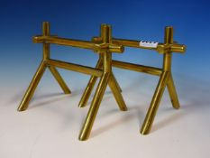 A PAIR OF CHRISTOPHER DRESSER DESIGN BRASS FIRE IRON RESTS, THE INVERTED Y SHAPED ENDS EACH JOINED