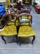 A SET OF SIX VICTORIAN ROSEWOOD BALLOON BACKED CHAIRS WITH BUTTONED GOLDEN VELVET SEATS AND CABRIOLE