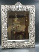AN ANTIQUE VICTORIAN HALLMARKED SILVER FRONTED EASEL BACKED MIRROR WITH A CHASED AND PIERCED