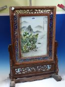 A CHINESE TABLE SCREEN, THE PORCELAIN PANEL PAINTED WITH A BOAT PUSHING OFF FROM A MOUNTAINOUS