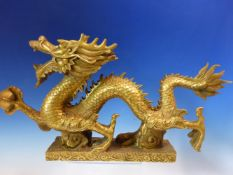 A CHINESE GILT METAL DRAGON STRIDING ACROSS THE RECTANGULAR CLOUD BASE HOLDING A SACRED PEARL. W