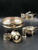 A GROUP OF HALLMARKED SILVER TO INCLUDE A WINE COASTER, THREE NAPKIN RINGS, A PEPPER, TWO MUSTARDS