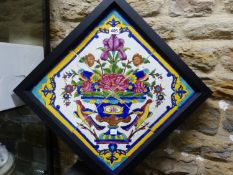 A FRAME OF FOUR PERSIAN TILES PAINTED WITH TWO BIRDS FLANKING A VASE OF FLOWERS WITHIN A BLUE,