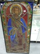 A VICTORIAN STAINED GLASS PANEL OF A SAINT STANDING IN A ROUND ARCHED NICHE, THE LEADED GLASS