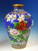 A CHINESE CLOISONNE ENAMEL MEIPING WORKED WITH BIRDS AMONGST PEONIES BELOW MAGNOLIA ON A BLUE