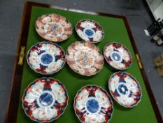 A PAIR OF FUKUGAWA IMARI FLUTED PLATES WITH CENTRAL VASES OF FLOWERS, SPIDER MARKS. Dia. 24cms.