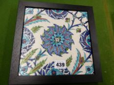 AN OTTOMAN STYLE KUTAHYA TILE, A TURQUOISE BORDERED BLUE FLOWER CENTRAL TO BUDS AND LEAVES, THE