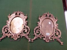 A PAIR OF GILT BRONZE EASEL BACKED FRAMES, THE OVAL OPENINGS ENCLOSED BY SCROLLS, FOLIAGE AND MASKS.