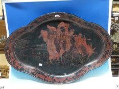 A CHINESE BLACK LACQUER QUATREFOIL TRAY PAINTED IN RED WITH THE DAOIST IMMORTALS ON A CLOUD WITHIN A