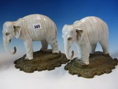A PAIR OF ANTIQUE GERMAN PORCELAIN ELEPHANTS STANDING ON LATER ORMOLU BASES. W 26cms.