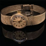 A LADIES 9ct GOLD VINTAGE OMEGA WATCH, ON AN INTEGRAL MILANESE 9ct GOLD BRACELET WITH A LADDER