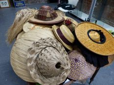 SIXTEEN HATS OF STRAW LEAVES AND GRASSES LABELLED FOR THEIR ORIGINS IN THE WORLD AND WHEN THEY