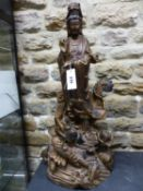 A CARVED AND GILT WOOD FIGURE OF GUANYIN STANDING ABOVE A WAVE SWEPT DRAGON, HER BOTTLE OF DEW