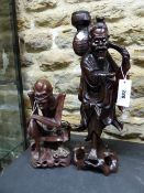 TWO CHINESE CARVED HARDWOOD FIGURES, ONE OF A SKINNY MAN SEATED. H 28cms. THE OTHER OF A