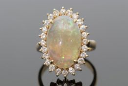 Opal and diamond dress ring, the oval shaped cabochon opal raised within a small diamond surround,