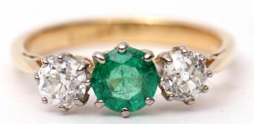 Emerald and diamond three-stone ring, the centre a circular shaped faceted emerald between two old