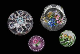 Group of paperweights including three Perthshire weights with multi-coloured designs and a