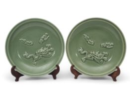 Two Longquan celadon chargers, both decorated in relief with dragons chasing the flaming pearl, 37cm