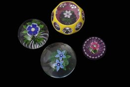 Group of four paperweights including a Baccarat primrose weight with a blue flower with white