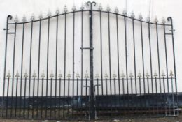 Large pair of wrought iron entrance gates of upright rail form with gilt pike detail and with arched