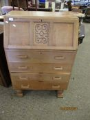 OAK FRAMED BUREAU WITH CARVED PANEL WITH DROP FRONT OVER FOUR FULL WIDTH DRAWERS RAISED ON TURNED