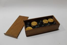 Mahogany case containing vintage draughts pieces and dominoes