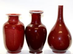 Group of three Chinese sang de beouf vases, one of bottle shape with tapered neck, the other two